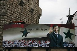 Billboard with a portrait of Bashar al-Assad and the text 'Syria is protected by God' on the old city wall of Damascus in 2006