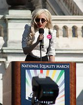 A blond woman speaking on a kiosk. She wears a  white shirt and black glasses. Behind her, the balcony of a building is  visible.