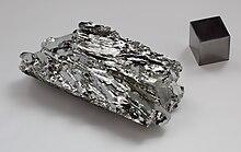 Molybdenum crystaline fragment and 1cm3 cube.jpg