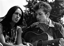 A black and white photograph of Joan Baez and Bob Dylan singing while Dylan plays guitar