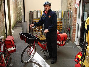Royal mail bicycle messenger in Ilminster, UK