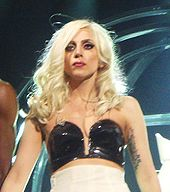 Upper torso of a young blond woman. Her hair  falls in waves up to her shoulders. She wears a black shiny bustier and a  white wrapping is visible underneath it. On her left hand, just below  her underarm, a tattoo is visible.