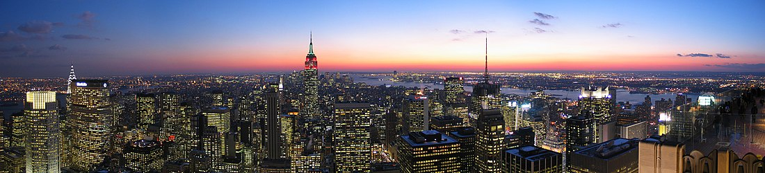 New York skyline at sunset, most of the blocky buildings with their windows lit up, and centered on a Empire State Building lit up red at its top.