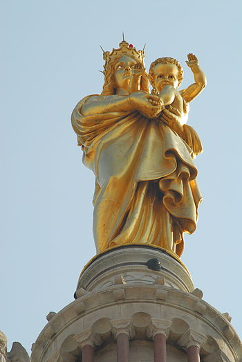 The golden statue on top of Notre Dame de la G...