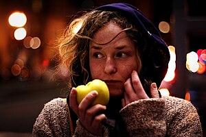 English: A woman eating an apple Français : Un...