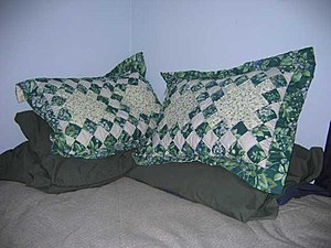 pillows piled in the corner of a bed