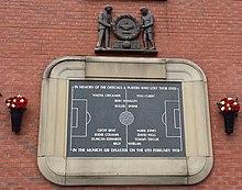 Une tablette de pierre, gravée à l'image d'un terrain de football et de plusieurs noms. Il est entouré d'une bordure de pierre en forme de stade de football. Au-dessus de la tablette, une sculpture en bois de deux hommes tenant une grande couronne.