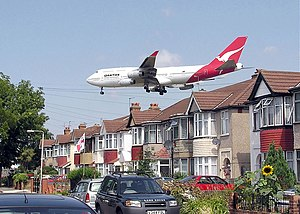 A landing Qantas Boeing 747-400 passes close t...