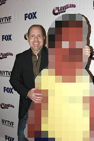 Voice actor Mike Henry posing with a cut-out o...