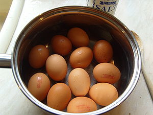 A dozen boiled eggs with lion marks visible in...