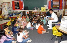US Navy 030512-N-7217H-001 Mess Management Specialist Gui Gagui, Armed Forces Committee Chairperson, reads a book to a group of 1st grade students at E.J. King Elementary School