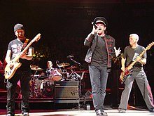 A color photograph of members of the band U2 performing on stage