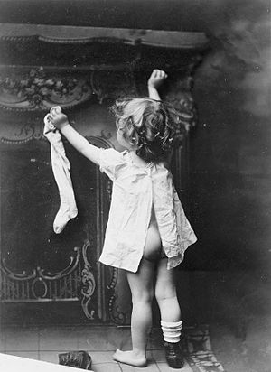 Little girl hanging up stocking by fireplace.