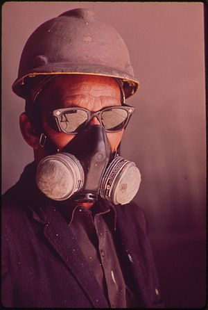 A SPRAY PAINTER AT THE AVONDALE SHIPYARD WEARS...