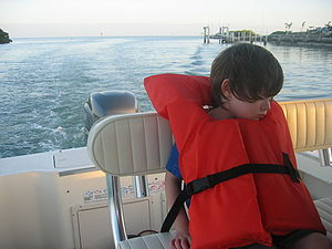 Young child sleeping at the back of a pontoon ...
