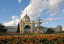 Gedung putih berornamen dengan kubah tinggi di tengah, di depannya terdapat air mancur emas dan bunga jingga