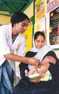 A mother holds her baby while it is immunized