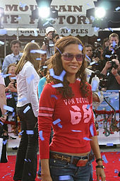 Upper body shot of Berry in long sleeved red jersey and jeans with midriff slightly exposed. A crowd in is the background.
