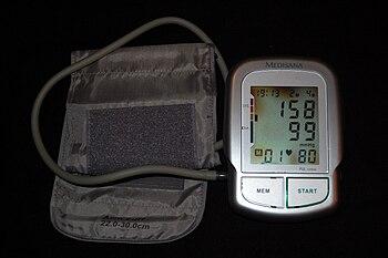 Automatic brachial sphygmomanometer showing grade 2 arterial hypertension (systolic blood pressure 158 mmHg, diastolic blood pressure 99 mmHg). Heart rate shown is 80 beats per minute.