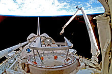 """A shuttle in space, with Earth in the background. A mechanical arm labelled """"Canada"""" rises from the shuttle"""