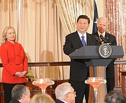Xi giving a speech at the U.S. Department of State in 2012, with Secretary of State Hillary Clinton and Vice-President Joe Biden in the background. Seated in the front row is former Secretary of State Henry Kissinger.