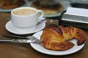 Español: Un café con leche y un cruasán.