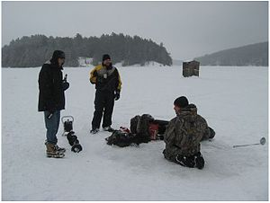 People ice fishing on the frozen surface of wh...