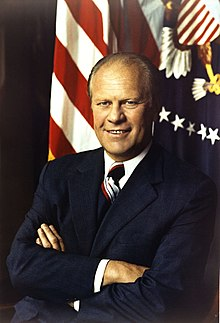 President Gerald Ford, arms folded, in front of a United States Flag and the Presidential seal.