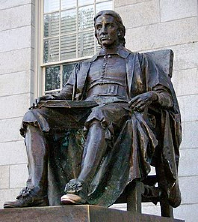 A bronze sculpture, on a tall granite plinth, of a man sitting in a chair with an open book in his lap. The statue as a whole is darkly weathered, but the toe of the figure's left shoe is shiny as if from frequent rubbing.