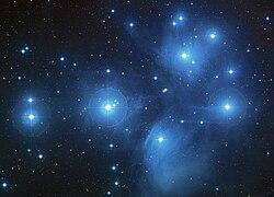 Imagen de las Pléyades, cúmulo estelar situado en la constelación de Tauro, compuesto de siete cuerpos astronómicos principales. Las estrellas que lo componen surgieron hace unos 100 millones de años en el seno de una enorme nube molecular. En determinados lugares de dicha nube, la densidad ρ fue lo suficientemente intensa como para que el tensor de Ricci  venciera los efectos de la presión del gas e iniciara la compresión de éste. El resultado fue el nacimiento de las hermosas Siete Hermanas.
