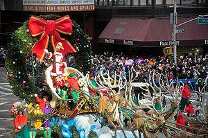 Santa Claus arrives, accompanied by his elves,...