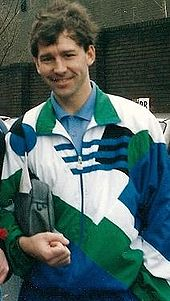 A smiling man with dark hair wearing a white, green and blue tracksuit top over a blue shirt. He is holding a washbag under his right arm.