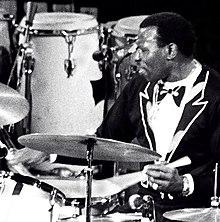 Elvin Jones in a black suit performing behind a drum kit