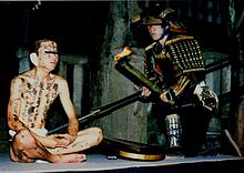 A man in black armor kneels beside a man clad only in a loincloth. The second man has black symbols painted on his body and bandages over his ears.