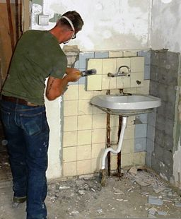 A U.S. Marine Corps combat engineer with Black Sea Rotational Force 2011 removes ceramic tiles during a renovation project at a senior citizens' home in Tbilisi, Georgia, July 20, 2011, during Agile Spirit 2011 110720-M-XX999-001
