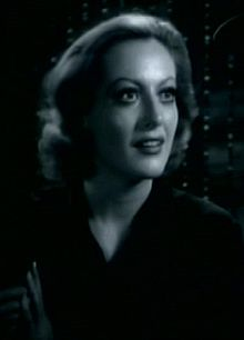 A studio publicity shot of  Crawford in dark clothes. Her face is highlighted; she smiling slightly and looking up.