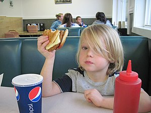 English: Child eating a veggie burger at a fas...