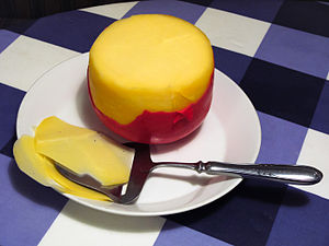 A small Edam cheese and a cheese-slicer.