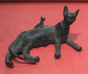 A bronze statue of a domesticated cat and her ...