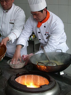 Preparing food near a wok stove.