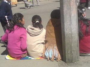 English: Aymara women sitting on the Wiphala i...