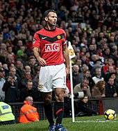 Un footballeur blanc aux cheveux courts, noirs et grisonnants. Il porte une chemise rouge, un short blanc, des chaussettes blanches et des chaussures de football blanches. Il court et a les joues gonflées.