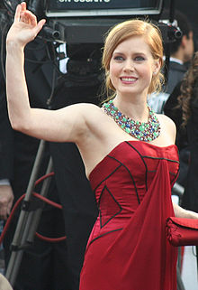 Young, blond woman wearing a red strapless dress and ornate gemstone necklace, smiling and waving
