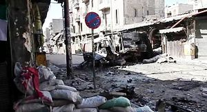 Destroyed vehicle on a devastated Aleppo street, 6 October 2012