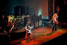 A color photograph of the band Led Zeppelin on stage