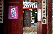 Hand-painted Chinese New Year's poetry pasted on the sides of doors leading to people's homes, Lijiang, Yunnan, China.