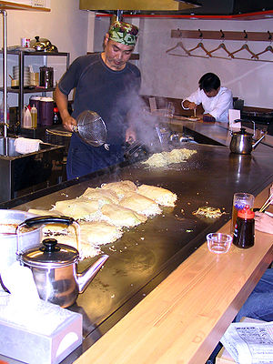 A man preparing okonomiyaki in a restaurant in...