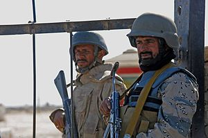 An Afghan border police officer, right, and a ...