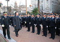 Macri, in an overcoat, walks down a line of young police officers