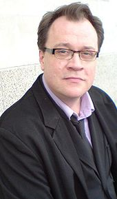 A bespectacled man in a black jacket, waistcoat, and tie, pink shirt, and jeans, sitting with his back to a marble-effect wall.